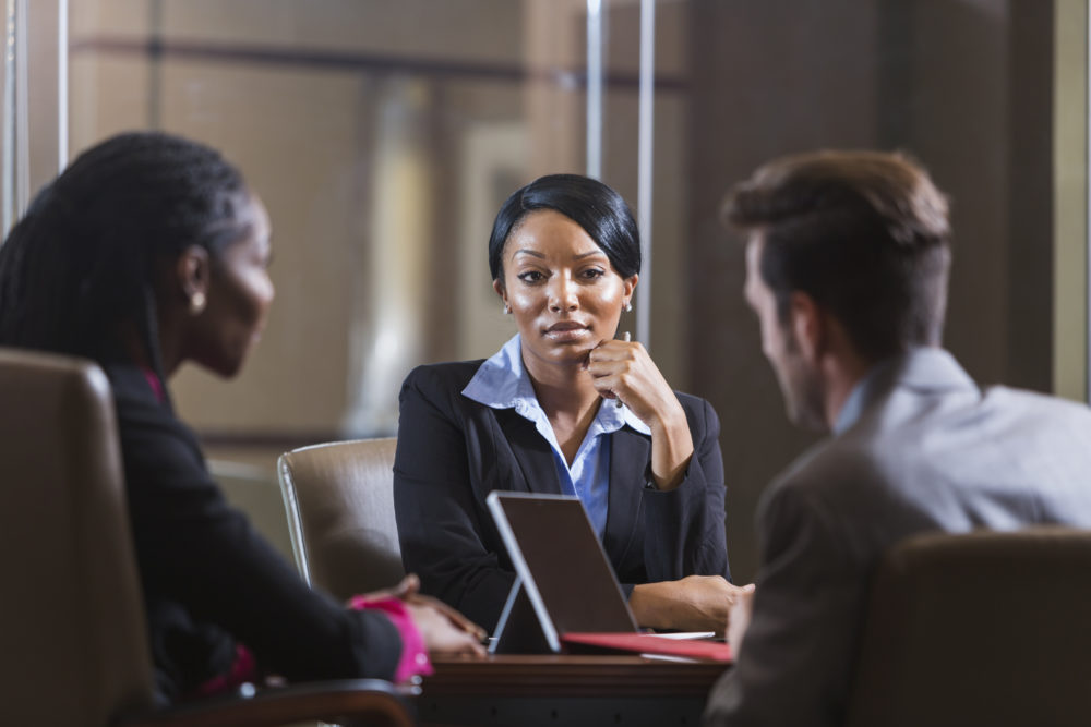 A group of three multi-ethnic businesspeople in a meeting in an office boardroom.  They are sitting, and there is a digital tablet on the table.  The focus is on the young African American woman with her hand on her chin, wearing a black suit.